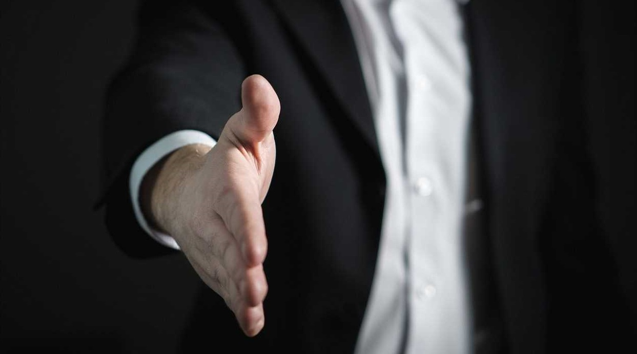 Man in suit stretching out hand for a handshake.