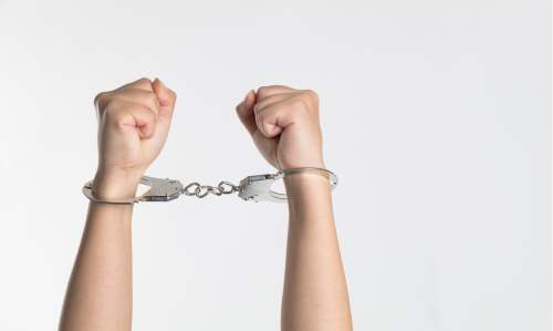 Person's hands in handcuffs