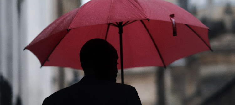 Dark sillhouette of a man holding a red umbrella.