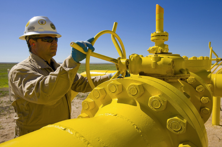 Worker maintaining a large yellow pipe