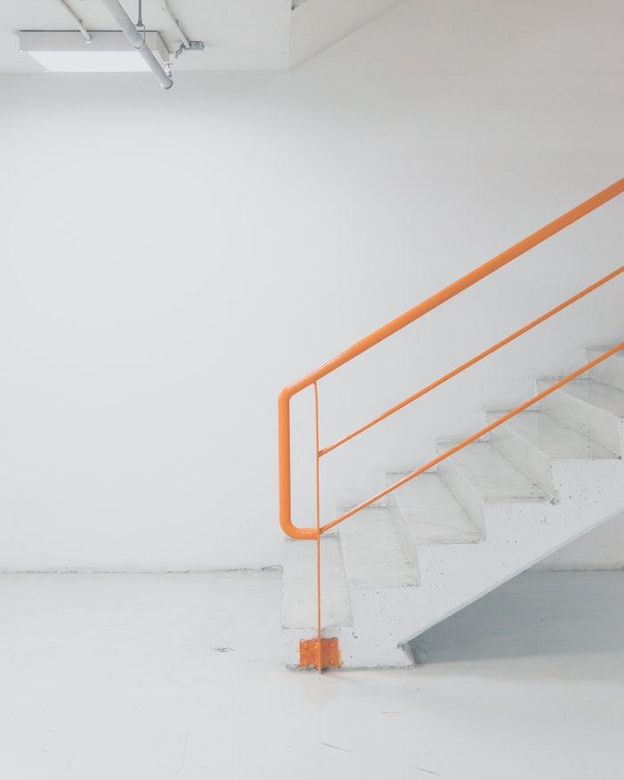 White stairs with an orange railing