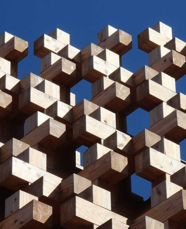 wooden building blocks stacked in a geometrical pattern against a clear blue sky