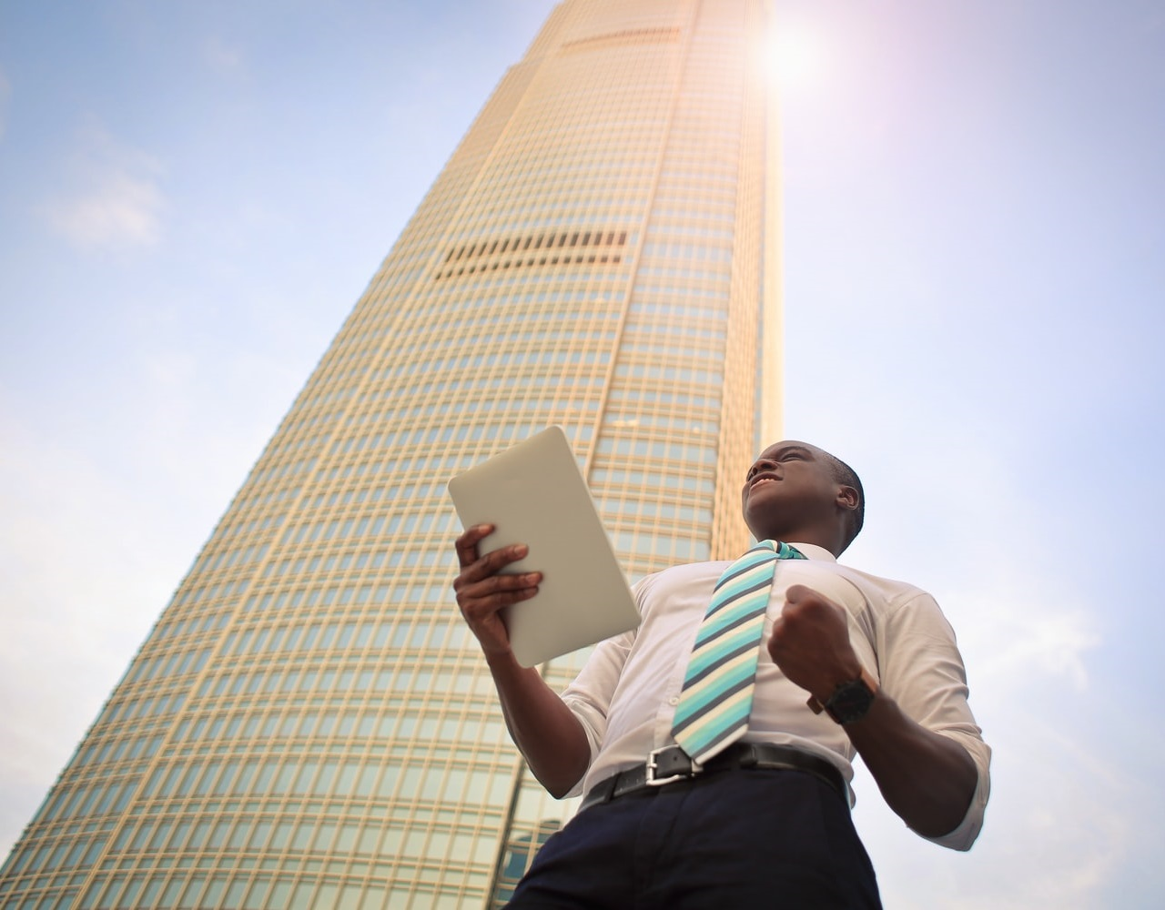 Photo of a tidily dressed young man holding documents, with the background of a tall building and a blue, sunny sky